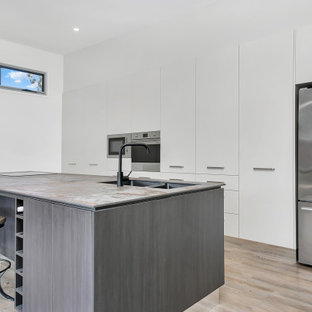 Photo of a contemporary galley kitchen in Cairns with an undermount sink, flat-panel cabinets, white cabinets, stainless steel appliances, light hardwood floors, a peninsula, beige floor and grey benchtop.