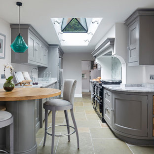Inspiration for a small classic galley kitchen/diner in Hampshire with a double-bowl sink, flat-panel cabinets, grey cabinets, marble worktops, mirror splashback, stainless steel appliances, limestone flooring, no island and beige floors.