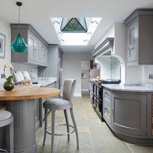 ハンプシャーの小さいトラディショナルスタイルのおしゃれなキッチン (ダブルシンク、フラットパネル扉のキャビネット、グレーのキャビネット、大理石カウンター、ミラータイルのキッチンパネル、シルバーの調理設備の、ライムストーンの床、アイランドなし、ベージュの床) の写真