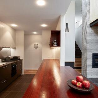 キャンベラの中サイズのモダンスタイルのおしゃれなキッチン (一体型シンク、黒いキャビネット、木材カウンター、メタリックのキッチンパネル、シルバーの調理設備の、セラミックタイルの床、黒い床、赤いキッチンカウンター) の写真