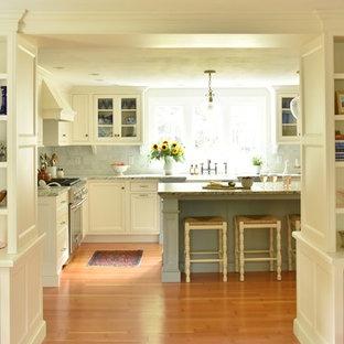 ボストンのおしゃれなアイランドキッチン (エプロンフロントシンク、インセット扉のキャビネット、御影石カウンター、大理石のキッチンパネル、パネルと同色の調理設備、淡色無垢フローリング) の写真