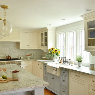 Design ideas for a rural l-shaped kitchen in Boston with a belfast sink, granite worktops, marble splashback, integrated appliances, an island, recessed-panel cabinets, white cabinets, grey splashback, medium hardwood flooring, brown floors and grey worktops.
