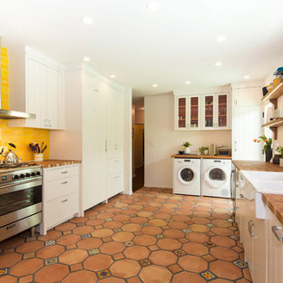 ロサンゼルスの地中海スタイルのおしゃれなコの字型キッチン (ドロップインシンク、フラットパネル扉のキャビネット、白いキャビネット、黄色いキッチンパネル、サブウェイタイルのキッチンパネル、シルバーの調理設備の、テラコッタタイルの床、アイランドなし) の写真