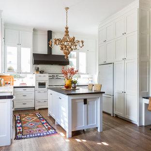 Foto di una cucina tradizionale di medie dimensioni con lavello sottopiano, ante in stile shaker, ante bianche, paraspruzzi bianco, paraspruzzi con piastrelle diamantate, elettrodomestici bianchi, parquet scuro, isola, top piastrellato e pavimento marrone