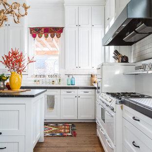 Mittelgroße Klassische Wohnküche in U-Form mit Schrankfronten im Shaker-Stil, weißen Schränken, Küchenrückwand in Weiß, Rückwand aus Metrofliesen, weißen Elektrogeräten, braunem Holzboden, Kücheninsel, braunem Boden und Arbeitsplatte aus Fliesen in Houston