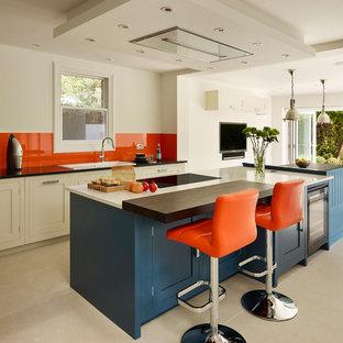 Klassische Küche mit Einbauwaschbecken, Schrankfronten im Shaker-Stil, Küchenrückwand in Orange, Glasrückwand und Kücheninsel in London