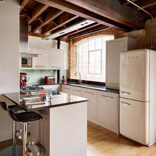 ロンドンの小さいエクレクティックスタイルのおしゃれなキッチン (アンダーカウンターシンク、フラットパネル扉のキャビネット、ベージュのキャビネット、ガラス板のキッチンパネル、白い調理設備、淡色無垢フローリング) の写真