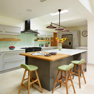 Eclectic kitchen in London with flat-panel cabinets, green splashback, subway tile splashback, stainless steel appliances and with island.