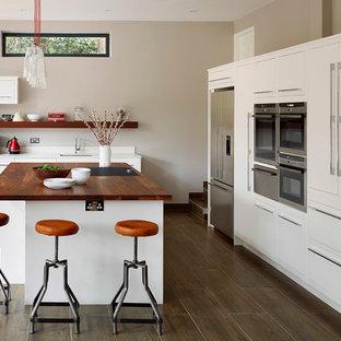 Modelo de cocina escandinava con fregadero bajoencimera, armarios con paneles lisos, puertas de armario blancas, encimera de madera, electrodomésticos de acero inoxidable, suelo de madera oscura y una isla