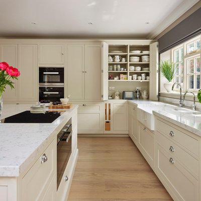 Transitional light wood floor kitchen photo in Oxfordshire with a farmhouse sink, flat-panel cabinets, beige cabinets, black appliances and an island