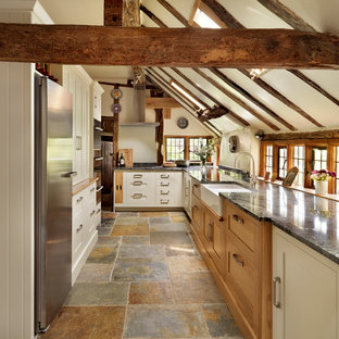 This is an example of a medium sized rural u-shaped kitchen in London with a belfast sink, shaker cabinets, white cabinets and stainless steel appliances.