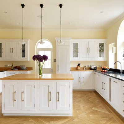 Example of a large classic u-shaped light wood floor kitchen design in London with an undermount sink, shaker cabinets, white cabinets, concrete countertops and an island