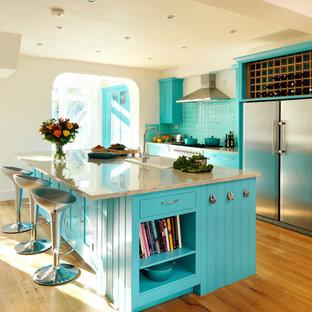 ロンドンのトランジショナルスタイルのおしゃれなキッチン (ドロップインシンク、青いキャビネット、青いキッチンパネル、シルバーの調理設備、無垢フローリング) の写真