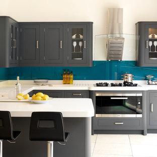 Идея дизайна: п-образная кухня в стиле современная классика с монолитной раковиной, фасадами в стиле шейкер, серыми фасадами, синим фартуком, фартуком из стекла, техникой из нержавеющей стали и полуостровом