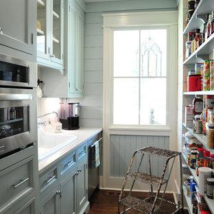 アトランタの中くらいのカントリー風おしゃれなキッチン (ドロップインシンク、シェーカースタイル扉のキャビネット、グレーのキャビネット、クオーツストーンカウンター、白いキッチンパネル、木材のキッチンパネル、シルバーの調理設備、濃色無垢フローリング、アイランドなし、茶色い床) の写真