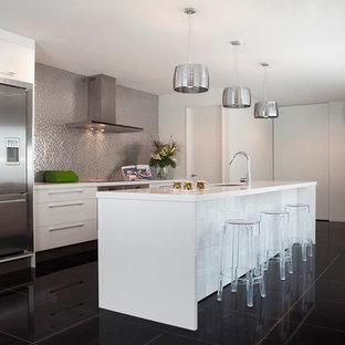 クライストチャーチの中サイズのモダンスタイルのおしゃれなキッチン (アンダーカウンターシンク、フラットパネル扉のキャビネット、黄色いキャビネット、グレーのキッチンパネル、シルバーの調理設備) の写真