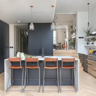 This is an example of a large scandi open plan kitchen in London with an integrated sink, marble worktops, white splashback, ceramic splashback, stainless steel appliances, light hardwood flooring, a breakfast bar, beige floors and white worktops.