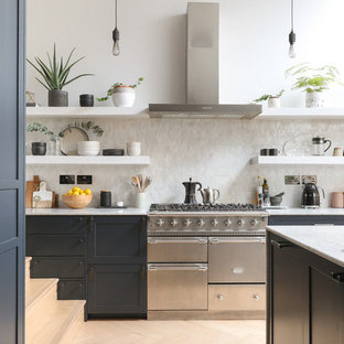 Large scandinavian open plan kitchen in London with an integrated sink, marble benchtops, white splashback, ceramic splashback, stainless steel appliances, light hardwood floors, a peninsula, beige floor and white benchtop.