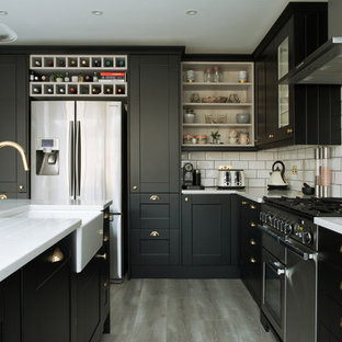 Design ideas for a traditional kitchen in London with a belfast sink, shaker cabinets, black cabinets, white splashback, metro tiled splashback, stainless steel appliances, an island, grey floors and white worktops.
