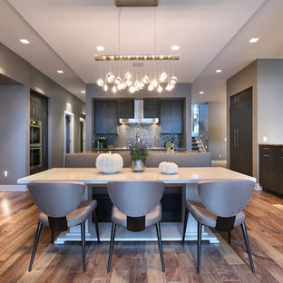 Large contemporary eat-in kitchen pictures - Example of a large trendy galley medium tone wood floor eat-in kitchen design in Grand Rapids with flat-panel cabinets, dark wood cabinets, multicolored backsplash, paneled appliances and an island