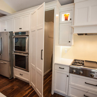 This is an example of a large classic l-shaped kitchen pantry in Salt Lake City with a belfast sink, shaker cabinets, white cabinets, engineered stone countertops, stainless steel appliances, dark hardwood flooring and an island.