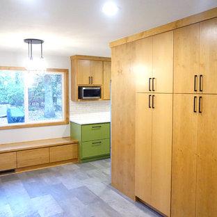 ポートランドの中サイズのミッドセンチュリースタイルのおしゃれなII型キッチン (エプロンフロントシンク、フラットパネル扉のキャビネット、中間色木目調キャビネット、クオーツストーンカウンター、白いキッチンパネル、磁器タイルのキッチンパネル、シルバーの調理設備の、クッションフロア、グレーの床、白いキッチンカウンター) の写真