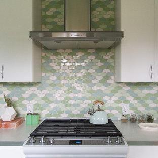 Inredning av ett 60 tals litet vit vitt kök, med en nedsänkt diskho, släta luckor, vita skåp, laminatbänkskiva, flerfärgad stänkskydd, stänkskydd i keramik, färgglada vitvaror, linoleumgolv och grönt golv