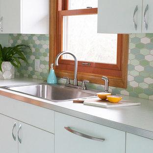 ポートランドの小さいミッドセンチュリースタイルのおしゃれなキッチン (ドロップインシンク、フラットパネル扉のキャビネット、白いキャビネット、ラミネートカウンター、マルチカラーのキッチンパネル、セラミックタイルのキッチンパネル、カラー調理設備、リノリウムの床、アイランドなし、緑の床、白いキッチンカウンター) の写真