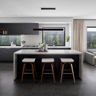 Photo of a contemporary l-shaped open plan kitchen in Melbourne with an undermount sink, flat-panel cabinets, grey cabinets, white splashback, mosaic tile splashback, stainless steel appliances, with island, grey floor and white benchtop.