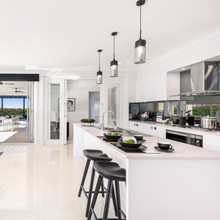 Large contemporary galley open plan kitchen in Other with a double-bowl sink, white cabinets, metallic splashback, mirror splashback, stainless steel appliances, ceramic floors, with island, white floor, flat-panel cabinets and turquoise benchtop.