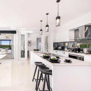 Пример оригинального дизайна: большая параллельная кухня-гостиная в современном стиле с двойной раковиной, белыми фасадами, фартуком цвета металлик, фартуком из зеркальной плитки, техникой из нержавеющей стали, полом из керамической плитки, островом, белым полом, плоскими фасадами и бирюзовой столешницей