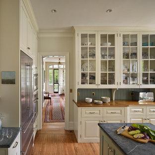 Idee per una cucina tradizionale con top in saponaria, ante di vetro, ante beige e elettrodomestici in acciaio inossidabile