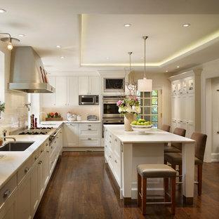 Imagen de cocina en L, clásica, con fregadero bajoencimera, armarios con paneles empotrados, puertas de armario blancas, salpicadero blanco, salpicadero de azulejos tipo metro y electrodomésticos de acero inoxidable