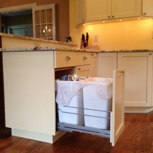 This is an example of a medium sized country galley kitchen/diner in Philadelphia with a belfast sink, shaker cabinets, yellow cabinets, granite worktops, white splashback, metro tiled splashback, stainless steel appliances, medium hardwood flooring and a breakfast bar.