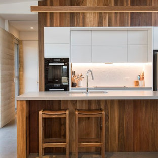 Photo of a contemporary galley kitchen in Other with a double-bowl sink, flat-panel cabinets, white cabinets, white splashback, black appliances, concrete floors, with island, grey floor and grey benchtop.