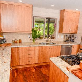 Mittelgroße Tropische Küche mit flächenbündigen Schrankfronten, hellen Holzschränken, Granit-Arbeitsplatte, Küchenrückwand in Beige, Rückwand aus Keramikfliesen, Küchengeräten aus Edelstahl, braunem Holzboden und Kücheninsel in Hawaii