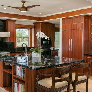 ハワイのトロピカルスタイルのおしゃれなキッチン (アンダーカウンターシンク、フラットパネル扉のキャビネット、中間色木目調キャビネット、黒いキッチンパネル、パネルと同色の調理設備、ベージュの床、御影石カウンター、セラミックタイルの床) の写真