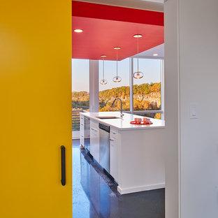 ワシントンD.C.の小さいコンテンポラリースタイルのおしゃれなキッチン (フラットパネル扉のキャビネット、白いキャビネット、シルバーの調理設備、アンダーカウンターシンク、珪岩カウンター、白いキッチンパネル、ガラスタイルのキッチンパネル、コンクリートの床) の写真