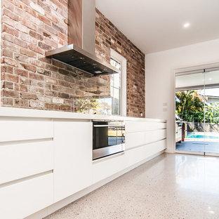 ブリスベンの広いモダンスタイルのおしゃれなキッチン (ドロップインシンク、フラットパネル扉のキャビネット、白いキャビネット、クオーツストーンカウンター、マルチカラーのキッチンパネル、レンガのキッチンパネル、黒い調理設備、セラミックタイルの床、マルチカラーの床、白いキッチンカウンター) の写真