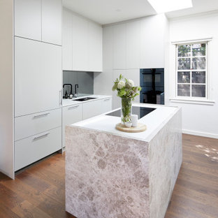 This is an example of a small contemporary l-shaped eat-in kitchen in Melbourne with a double-bowl sink, grey cabinets, metallic splashback, mirror splashback, black appliances, with island, white benchtop, quartz benchtops and brown floor.