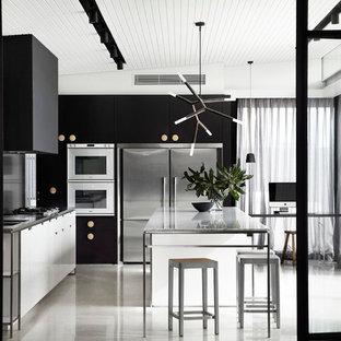 Diseño de cocina en L, contemporánea, con armarios con paneles lisos, puertas de armario negras, electrodomésticos de acero inoxidable y una isla