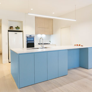 Contemporary galley open plan kitchen in Melbourne with a double-bowl sink, flat-panel cabinets, blue cabinets, wood benchtops, white splashback, white appliances, light hardwood floors, a peninsula and beige floor.