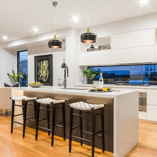 This is an example of a contemporary kitchen in Townsville with an undermount sink, flat-panel cabinets, white cabinets, window splashback, medium hardwood floors, with island and brown floor.