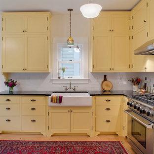 Foto di una cucina classica con paraspruzzi con piastrelle diamantate, lavello stile country, ante in stile shaker, ante gialle, paraspruzzi bianco, top in saponaria e elettrodomestici in acciaio inossidabile