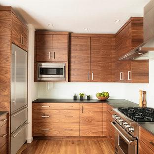 Bild på ett retro svart svart kök, med en undermonterad diskho, släta luckor, skåp i mellenmörkt trä, bänkskiva i kvarts, vitt stänkskydd, glaspanel som stänkskydd, rostfria vitvaror, ljust trägolv, en halv köksö och brunt golv