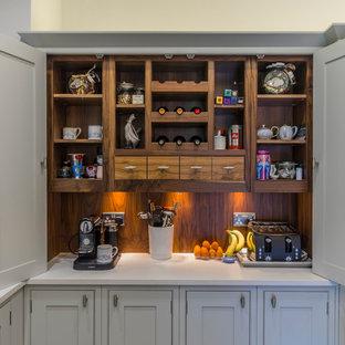 Ispirazione per una cucina abitabile classica di medie dimensioni con lavello sottopiano, ante grigie, paraspruzzi bianco, ante con bugna sagomata, top in marmo e un'isola