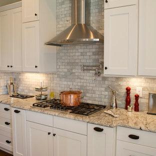 Mittelgroße, Geschlossene Klassische Küche in U-Form mit Landhausspüle, Schrankfronten im Shaker-Stil, weißen Schränken, Granit-Arbeitsplatte, Küchenrückwand in Grau, Rückwand aus Steinfliesen, Küchengeräten aus Edelstahl, braunem Holzboden und Kücheninsel in Raleigh