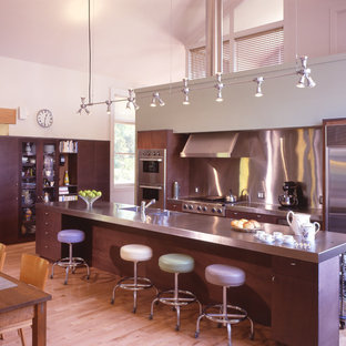 Mid-sized contemporary l-shaped eat-in kitchen in New York with an integrated sink, flat-panel cabinets, dark wood cabinets, stainless steel benchtops, metallic splashback, metal splashback, stainless steel appliances, light hardwood floors and with island.
