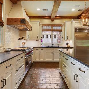 Esempio di una grande cucina country con lavello sottopiano, ante a filo, ante bianche, top in granito, paraspruzzi bianco, paraspruzzi con piastrelle in terracotta, elettrodomestici in acciaio inossidabile, pavimento in mattoni e isola