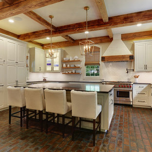 This is an example of a large country u-shaped kitchen pantry in New Orleans with an undermount sink, beaded inset cabinets, white cabinets, granite benchtops, white splashback, stainless steel appliances, brick floors, with island and subway tile splashback.